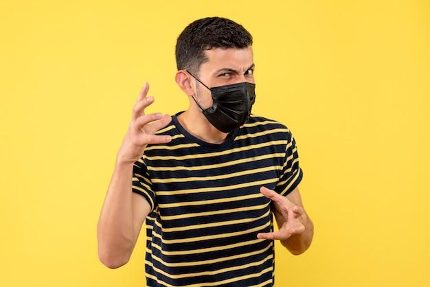 노란색 격리 된 배경에 서있는 검은 색과 흰색 줄무늬 티셔츠에 전면보기 젊은 남자