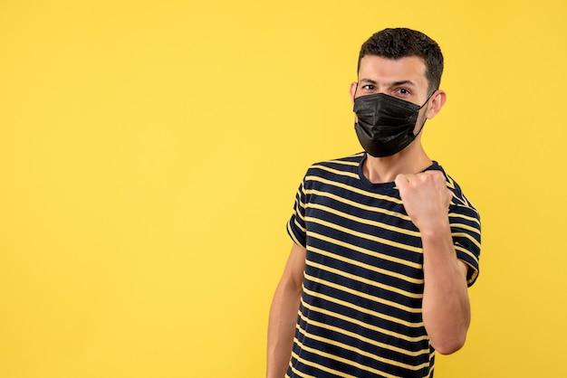 검은 색과 흰색 줄무늬 티셔츠 노란색 배경 복사 공간에 전면보기 젊은 남자