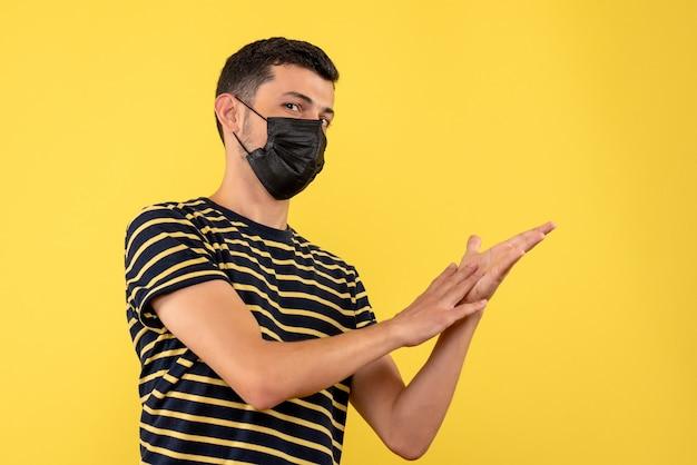 黒と白の縞模様のtシャツ黄色の背景の空き領域の正面図の若い男
