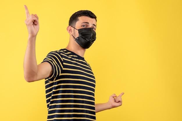 여유 공간이있는 검은 색과 흰색 줄무늬 티셔츠 노란색 배경에 전면보기 젊은 남자