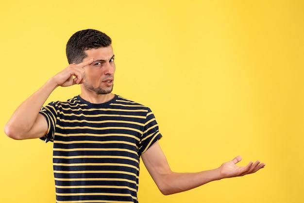 Вид спереди молодой человек в черно-белой полосатой футболке на желтом изолированном фоне с копией пространства