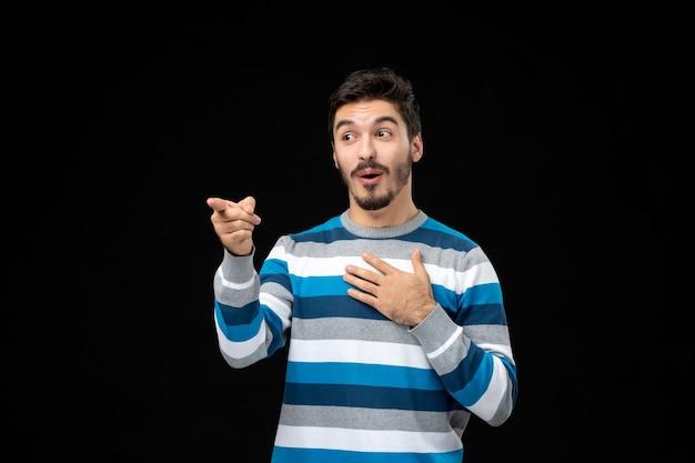誰かを指している青い縞模様のジャージの正面図の若い男