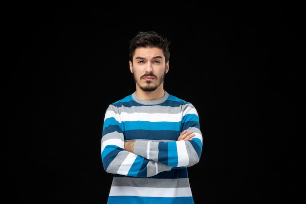 腕を組んでポーズをとる青い縞模様のジャージの正面図若い男