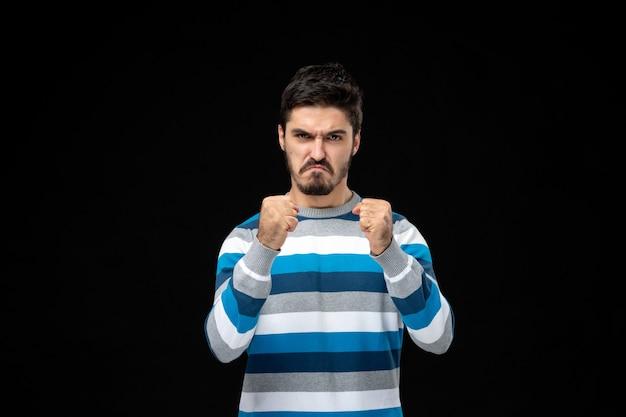 怒りの表情と青い縞模様のジャージの正面図の若い男
