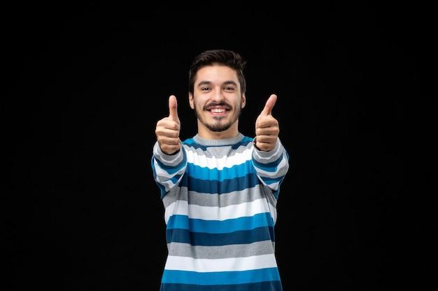 Вид спереди молодой человек в синей полосатой майке с большими пальцами руки вверх