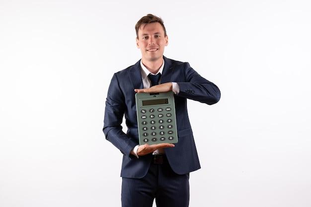 白い背景の上の巨大な計算機を保持しているエレガントな古典的なスーツの正面図若い男