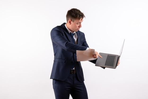 Вид спереди молодой человек в костюме, используя свой ноутбук и проверяя файлы на белом фоне