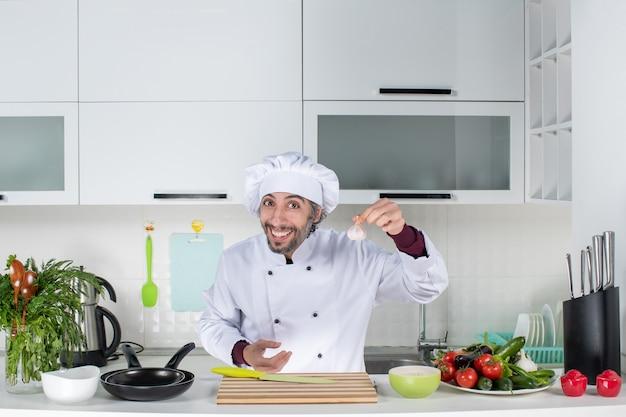 キッチンでニンニクを保持している制服姿の若い男正面図