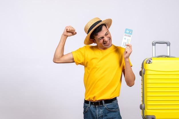 Вид спереди молодой человек в желтой футболке, стоящий возле желтого чемодана с билетом, выражающий его счастье