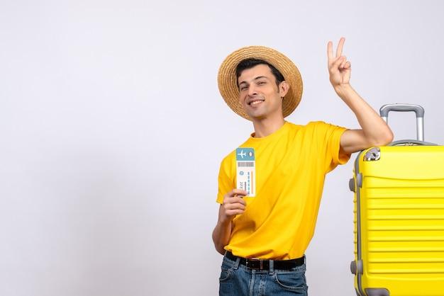 Вид спереди молодой человек в желтой футболке, стоящий возле желтого чемодана с билетом, делающий знак v