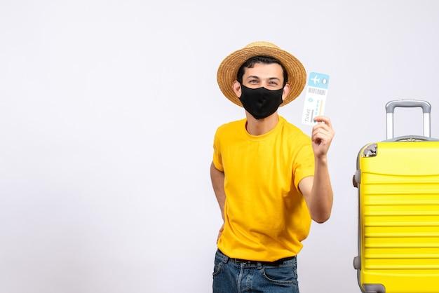Вид спереди молодой человек в желтой футболке, стоящий возле желтого чемодана, держащего авиабилет