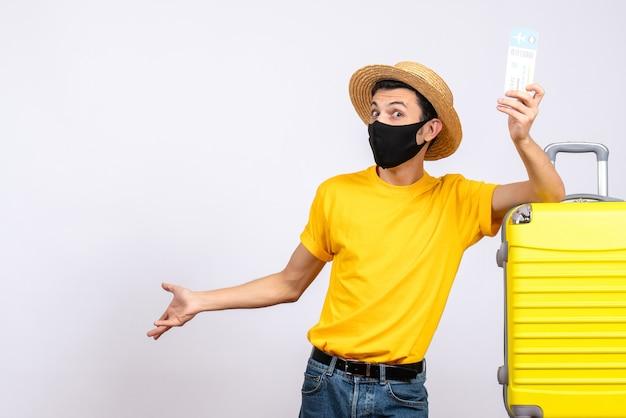 飛行機のチケットを保持している黄色のスーツケースの近くに立っている黄色のtシャツの正面図若い男