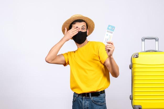 手で目を覆っている旅行チケットを保持している黄色のスーツケースの近くに立っている黄色のtシャツの正面図若い男