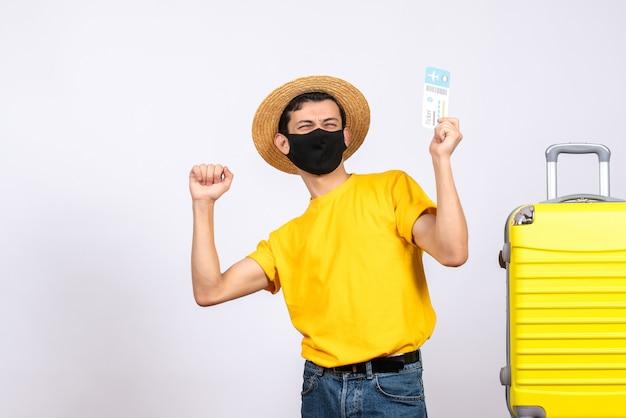 彼の幸せを表現する旅行チケットを保持している黄色のスーツケースの近くに立っている黄色のtシャツの正面図若い男