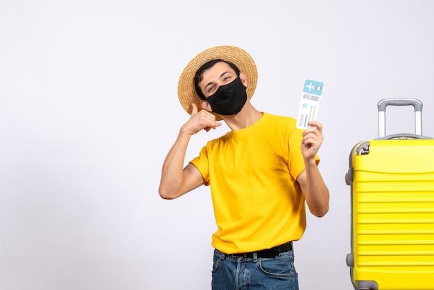 Вид спереди молодой человек в желтой футболке, стоящий возле желтого чемодана, держа проездной билет, делая знак