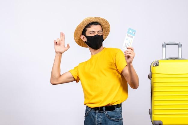指銃を作る旅行チケットを保持している黄色のスーツケースの近くに立っている黄色のtシャツの正面図若い男