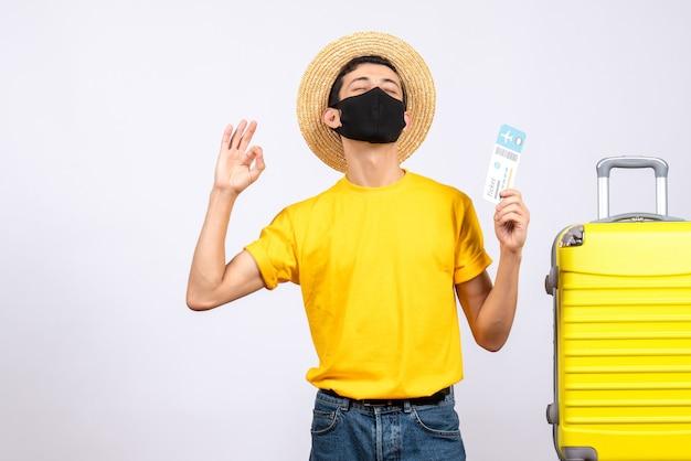 Вид спереди молодой человек в желтой футболке, стоящий возле желтого чемодана, держа проездной билет, делая знак ок