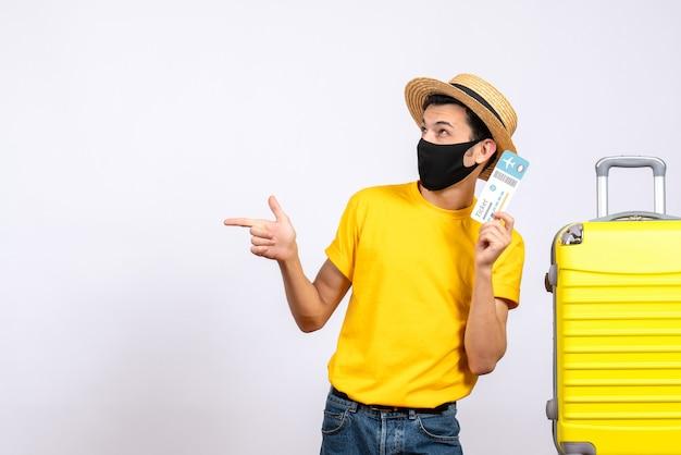 左向きの旅行チケットを保持している黄色のスーツケースの近くに立っている黄色のtシャツの正面図若い男