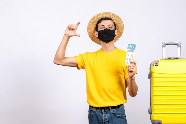 指でサイズを示す旅行チケットを保持している黄色のスーツケースの近くに立っている黄色のtシャツの正面図若い男