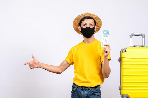旅行チケットを保持している黄色のスーツケースの近くに立っている黄色のtシャツの正面図若い男