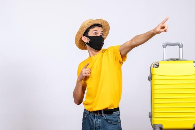 Вид спереди молодой человек в желтой футболке, стоящий возле желтого чемодана, указывая на что-то