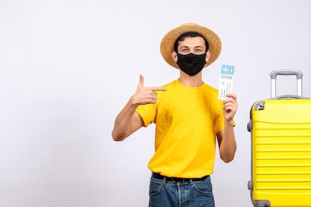 旅行チケットを指している黄色のスーツケースの近くに立っている黄色のtシャツの正面図若い男