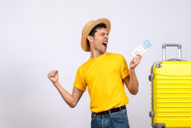Вид спереди молодой человек в желтой футболке, стоящий возле желтого чемодана, показывая свое счастье
