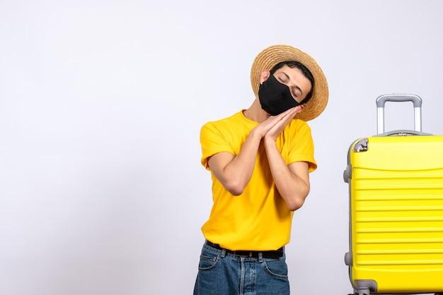 Вид спереди молодой человек в желтой футболке, стоящий возле спящего желтого чемодана