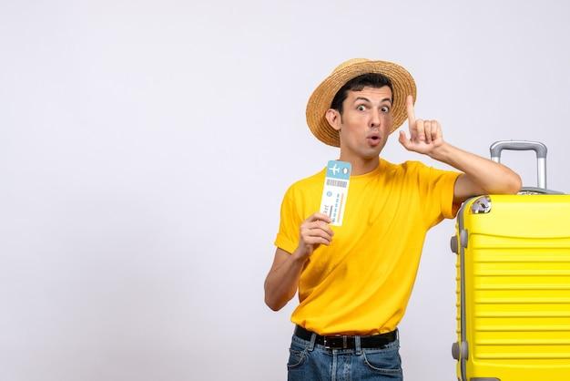 Вид спереди молодой человек в желтой футболке, стоящий возле желтого чемодана, удивляющий своей идеей