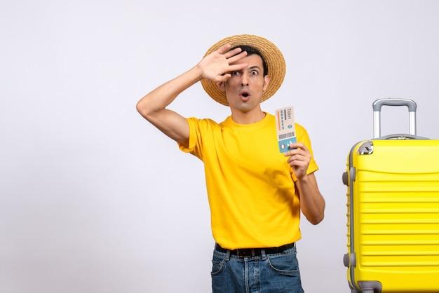 疑問に思っている黄色のスーツケースの近くに立っている黄色のtシャツの正面図若い男