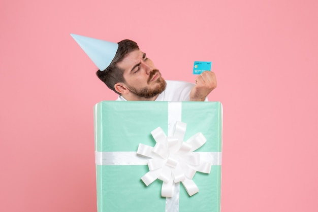 Front view of young man inside present box holding bank card on pink wall