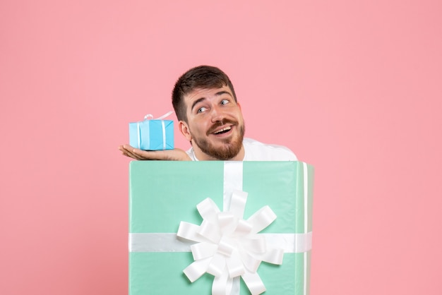 Front view of young man inside present box holding little gift on pink wall