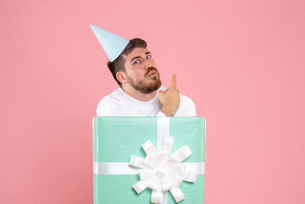 Front view of young man inside present box on pink wall