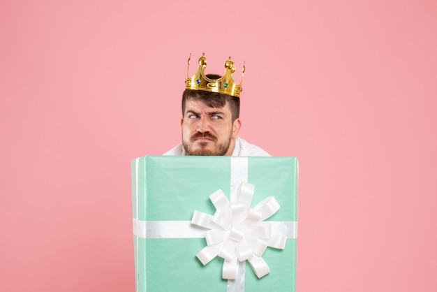 Front view of young man inside present box with crown on light pink wall