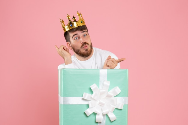 Front view of young man inside present box with crown on pink wall