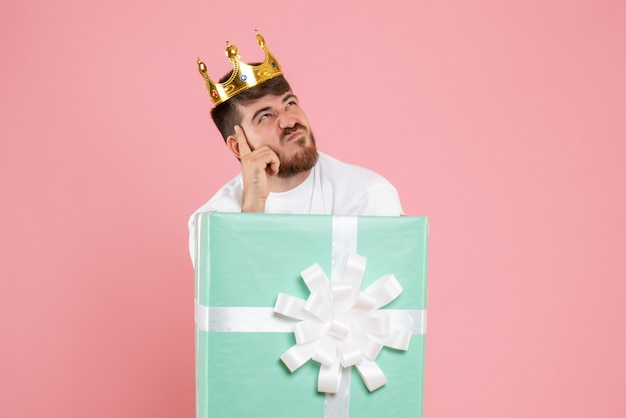 Front view of young man inside present box with crown thinking on pink wall