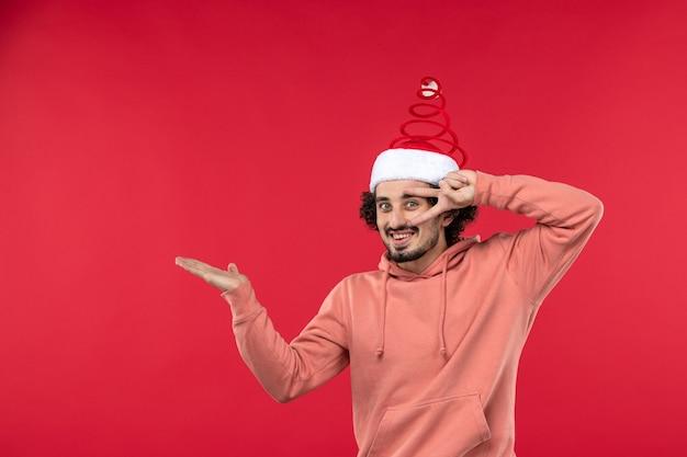 Vista frontale del giovane che sorride appena sulla parete rossa