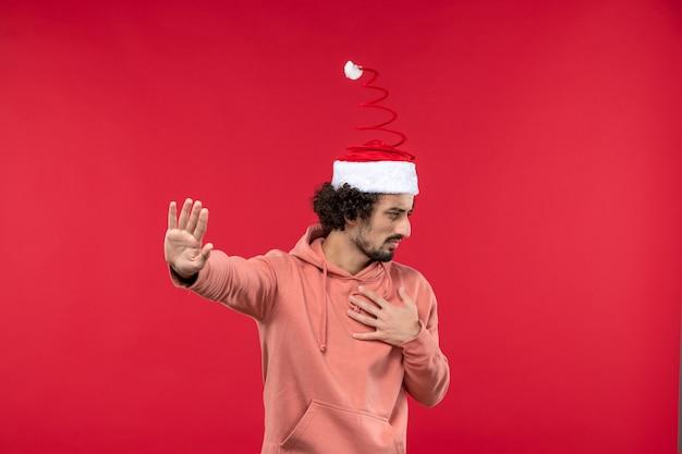 Vista frontale del giovane uomo solo in piedi sulla parete rossa