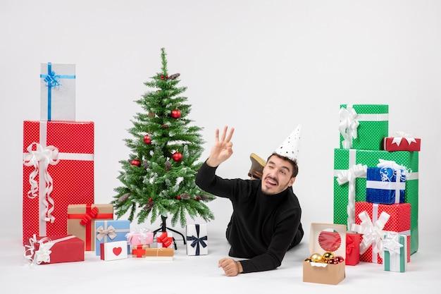 Vista frontale del giovane che pone intorno ai regali di festa su un muro bianco