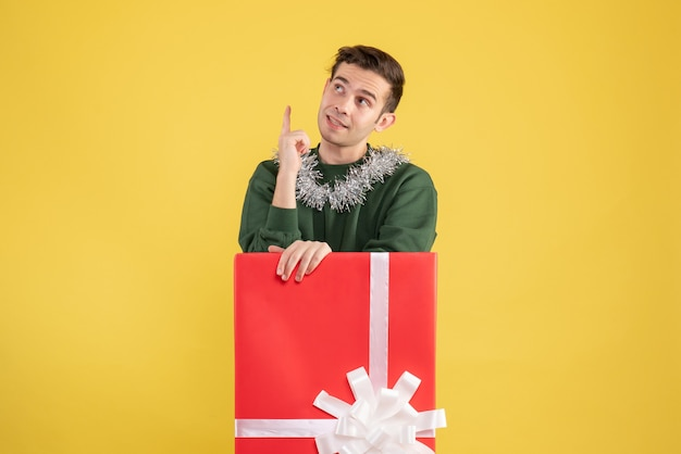 Front view young man looking at ceiling standing behind big giftbox on yellow