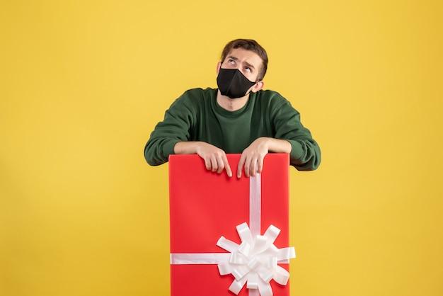 Vista frontale del giovane che guarda in su in piedi dietro il grande giftbox su giallo
