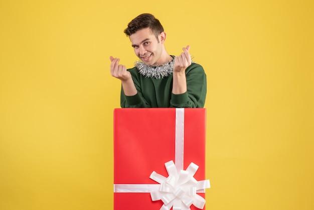 Вид спереди молодой человек делает корейский знак сердца, стоящий за большой подарочной коробкой на желтом