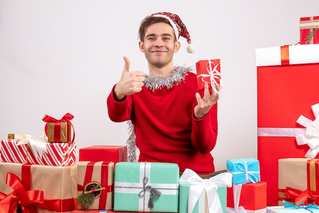 Front view young man making thumb up sign sitting around xmas gifts