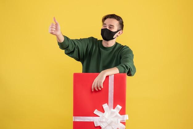 노란색에 큰 giftbox 뒤에 서 가입 엄지 손가락을 만드는 전면보기 젊은 남자