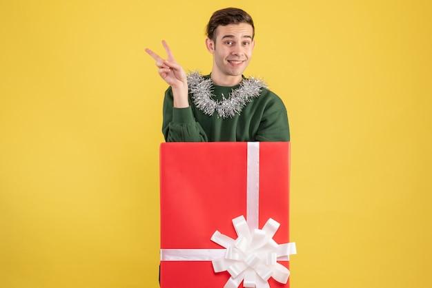 노란색에 큰 giftbox 뒤에 서있는 v 기호를 만드는 전면보기 젊은 남자