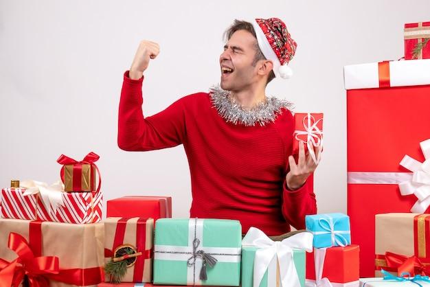 クリスマスプレゼントの周りに座って勝利のジェスチャーを作る正面図の若い男