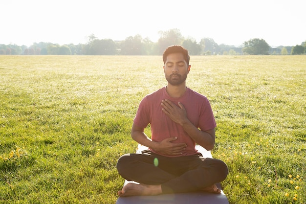 Front view of young man meditating outdoors on yoga mat