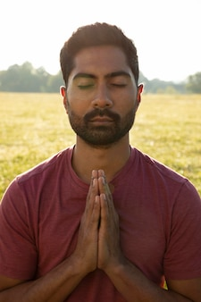 Front view of young man meditating outdoors