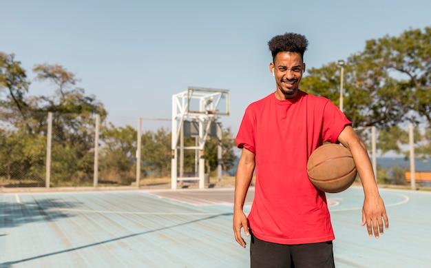 バスケットボールのフィールドに正面図の若い男