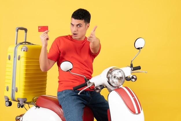 Вид спереди молодой человек на мопеде, держащий кредитную карту, указывая пальцем пистолет жестом на камеру